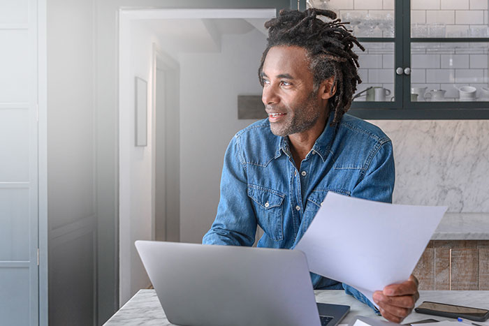 Confident businessman in his 50s working on laptop and paperwork
