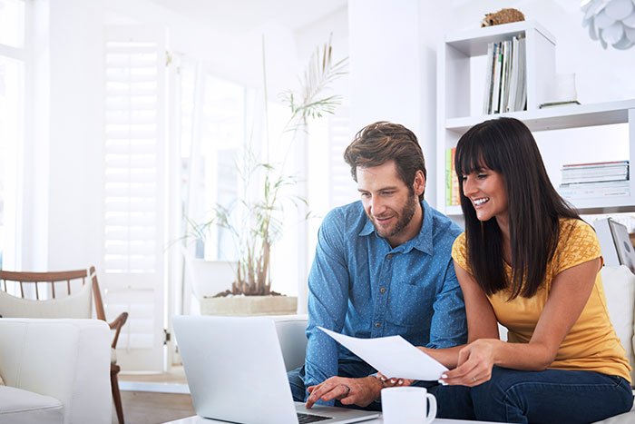 Couple using the laptop and smiling.