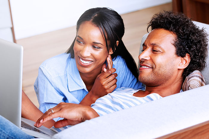 Happy couple relaxing on couch with laptop