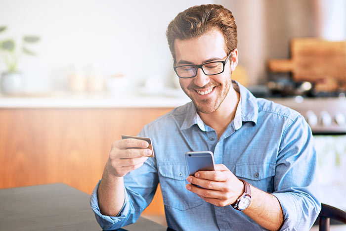 Young man using a cellphone and credit card at home