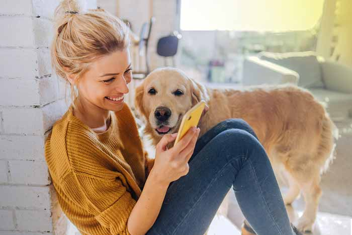 Young woman reading morning news online while her dog standing next to her