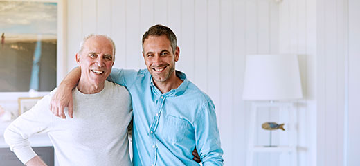Smiling father and son standing arm around at home