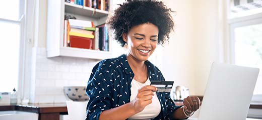 Young woman using credit card to purchase online