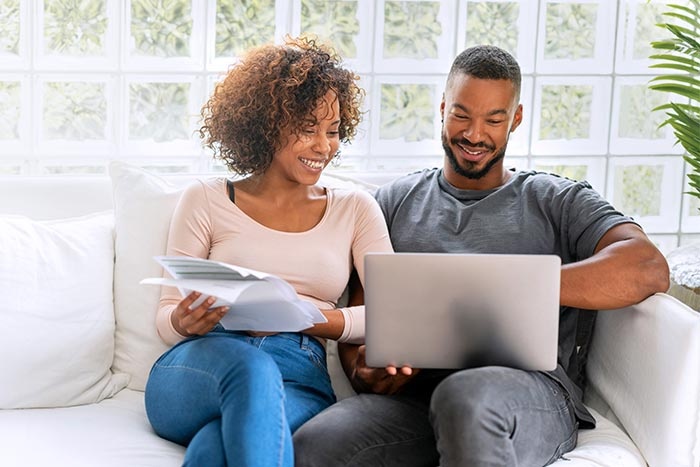 Loving couple paying bills online at home