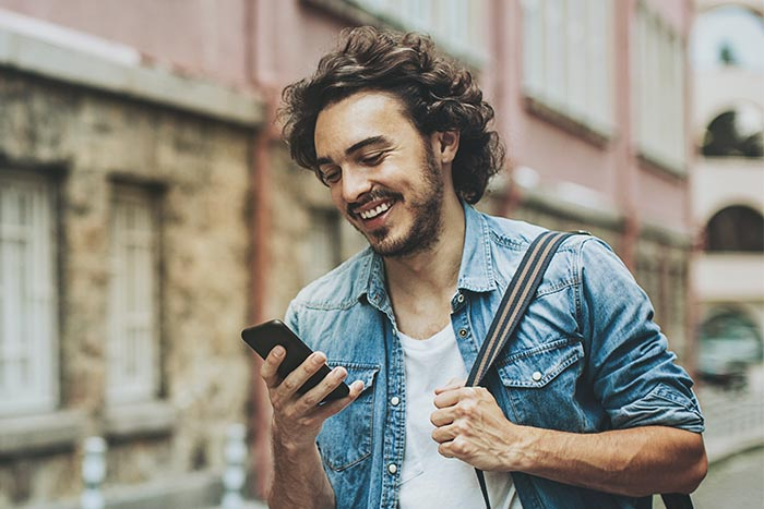 Smiling young man walking outdoors and looking at his phone