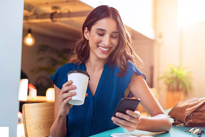 Young beautiful woman holding coffee and looking at smartphone