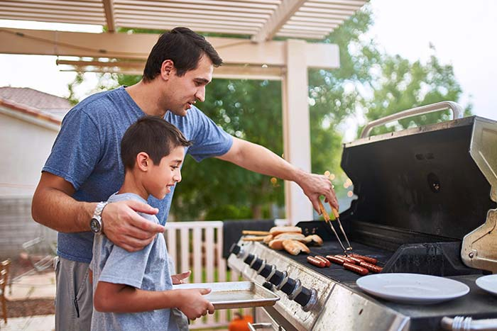 Father teaching son how to grill