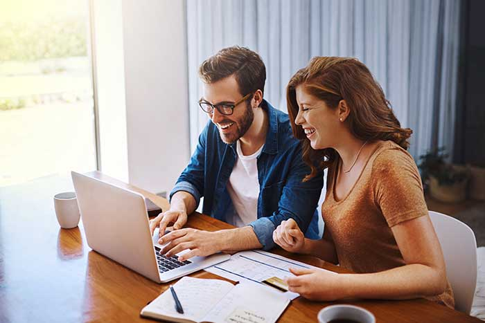 Young couple doing online shopping on a laptop together at home