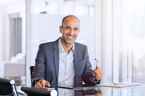 Mature business man smiling at his desk