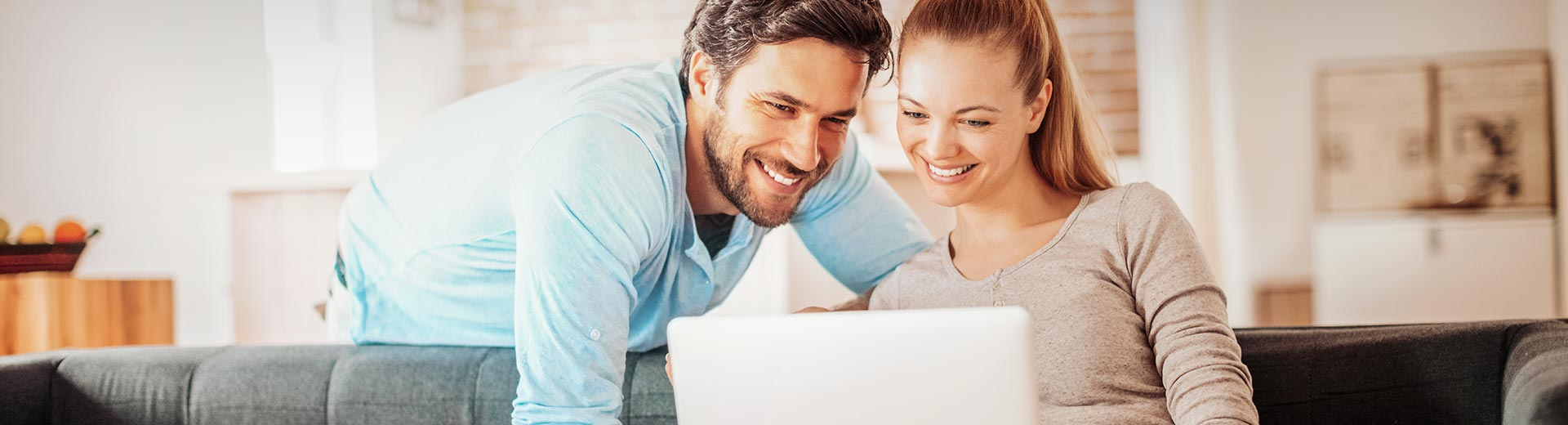 Happy young couple using laptop at home