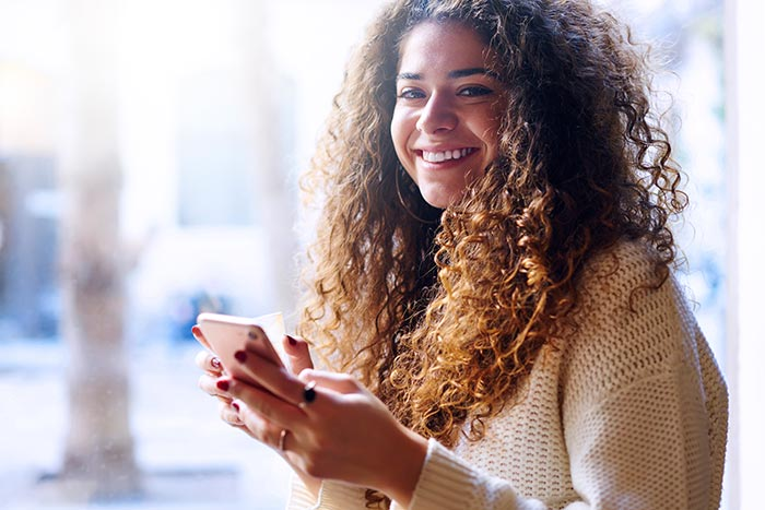 Cheerful young woman with curly hair spending time in cafe