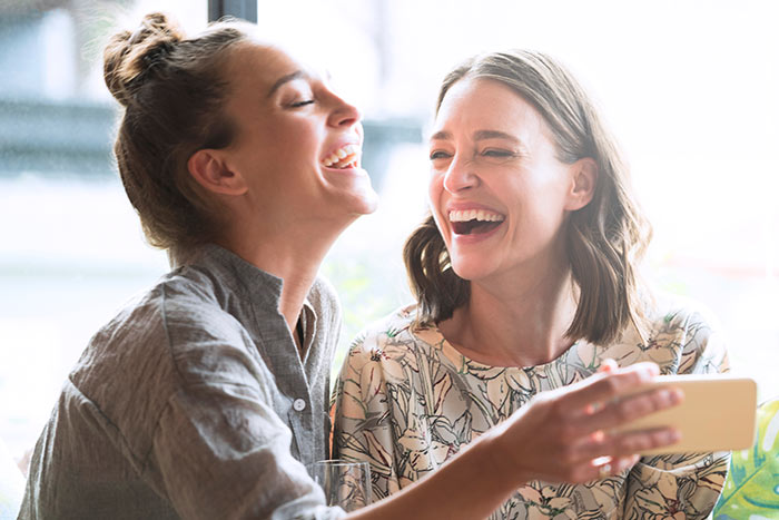 Woman holding mobile phone with friend laughing