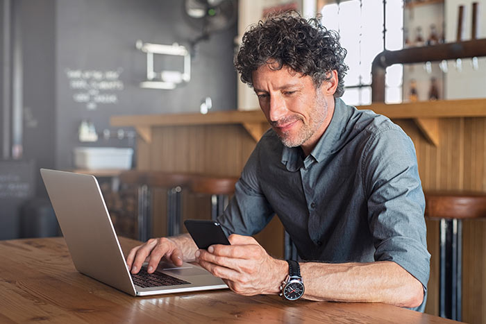 Happy mature man sitting at cafe with laptop