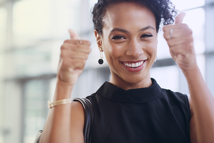Cropped shot of a young businesswoman showing thumbs up while walking through a modern office