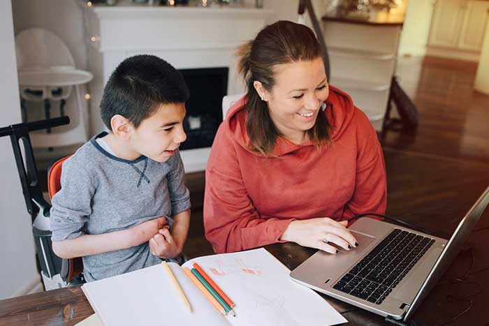 Smiling mother showing video to autistic son on laptop at home