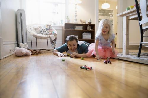 A father playing with his daughter with some toy cars
