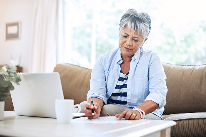 Senior woman doing paperwork at home