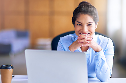 Woman sitting at desk in front of laptop smiling