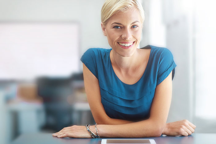 Lady crossing her arm, leaning forward on her desk and smiling.