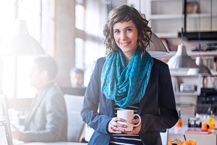 Lady wearing a blue scarf smiling and holding on to a coffee cup.