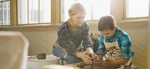 Female teacher assisting boy in pottery class