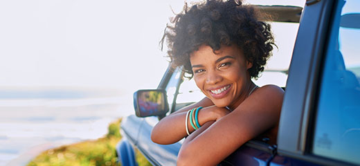 Young woman parked on a beach looking out car window